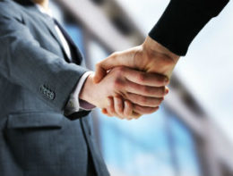 Two businessmen shaking hands in a deal.