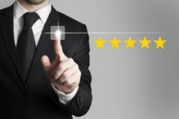 Man using touchscreen to give five star review.